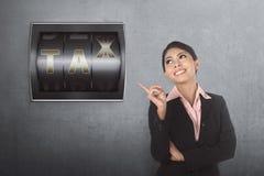 Piękna azjatykcia biznesowa kobieta wskazuje odpierającą cyfrę z podatkiem s Fotografia Royalty Free