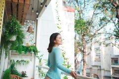 Piękna azjatykcia dziewczyna cieszy się świeżość na balkonie obraz royalty free