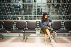 Piękna azjatykcia dziewczyna patrzeje jej zegarek, czeka wsiadać samolot, czasu pojęcie fotografia royalty free
