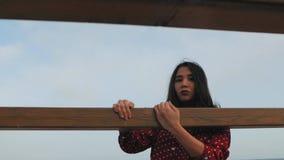 Piękna azjatykcia dziewczyna rusza się jej ręki na drewnianej ramie