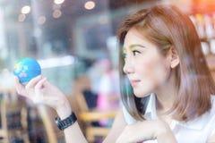 Piękna azjatykcia dziewczyna trzyma kulę ziemską w jej ręce w cofffee sho Obrazy Stock