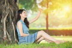 Piękna azjatykcia kobieta bierze selfie obsiadanie na trawie fotografia royalty free