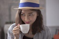 Piękna azjatykcia kobieta i gorącego filiżanki szczęścia uśmiechnięta twarz Obrazy Stock