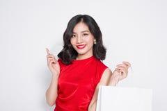 Piękna azjatykcia kobieta jest ubranym czerwoną suknię z torba na zakupy i Obrazy Royalty Free