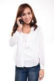 Piękna azjatykcia kobieta opowiada na telefonie komórkowym, odizolowywającym na bielu Obraz Royalty Free