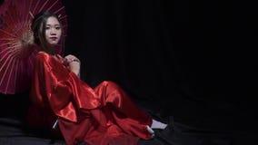 Piękna azjatykcia kobieta w kimonie z parasola spojrzeniami w kamerę, zwolnione tempo zbiory