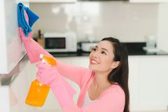 Piękna azjatykcia kobieta w ochronnych rękawiczkach czyści kuchni cabi Zdjęcia Stock
