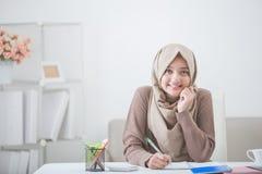Piękna azjatykcia kobieta z kierowniczym szalika writing coś Obrazy Royalty Free