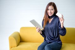 Piękna azjatykcia młoda kobieta pokazuje kartę kredytową trzyma cyfrową pastylkę online komputerowy zakupy wow uśmiechnięta z pod obraz royalty free