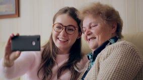 Piękna babcia i córka robimy selfie i my uśmiechamy się podczas gdy siedzący na leżance w domu zbiory