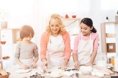 Piękna babcia wraz z szczęśliwymi wnukami w kuchni, rozdrobni ciasto dla wypiekowych ciastek Zdjęcie Stock