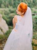 Piękna bajecznie szczęśliwa redhair panna młoda patrzeje nad ramieniem na tle Carpathians góry Obraz Stock
