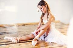 Piękna balerina wiąże pointe baletniczych buty przy szkołą taniec fotografia stock
