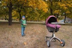 Piękna berbeć chłopiec bawić się z spacerowiczem Zdjęcia Royalty Free