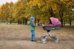 Piękna berbeć chłopiec bawić się z spacerowiczem Obrazy Royalty Free