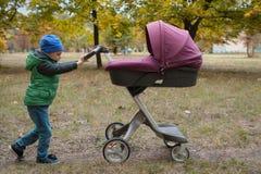 Piękna berbeć chłopiec bawić się z spacerowiczem Zdjęcie Royalty Free