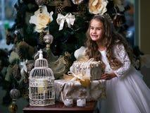 Piękna bezzębna dziewczyna w biel sukni cieszy się prezenty Zdjęcia Stock