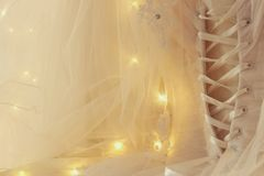 Piękna biała ślubna suknia i przesłona na krześle z girlandą zaświecamy zdjęcie stock