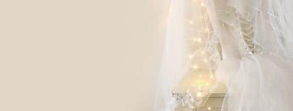 Piękna biała ślubna suknia i przesłona na krześle z złocistą girlandą zaświecamy zdjęcie royalty free