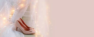 Piękna biała ślubna suknia i przesłona na krześle z złocistą girlandą zaświecamy zdjęcia royalty free