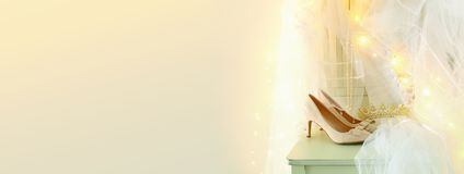 Piękna biała ślubna suknia i przesłona na krześle z złocistą girlandą zaświecamy zdjęcie stock
