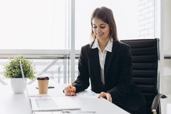 Piękna biznesowa dama jest przyglądającym laptopem i ono uśmiecha się podczas gdy pracujący w biurze Koncentrujący na pracie zdjęcie stock