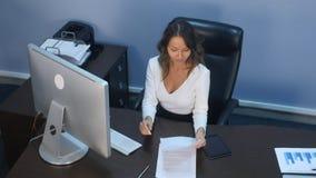 Piękna biznesowa dama pracuje z cyfrową pastylką i dokumentami w biurze Fotografia Royalty Free