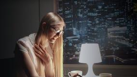 Piękna biznesowa dama w eyeglasses pokazuje coś na smartphone zdjęcie wideo