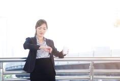Piękna biznesowa kobieta trzyma filiżankę kawy i sprawdza th Obrazy Stock
