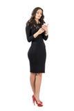 Piękna biznesowa kobieta w eleganckiego czerni smokingowy pisać na maszynie na jej smartphone Zdjęcie Royalty Free