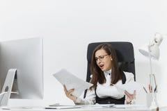 Piękna biznesowa kobieta w kostiumu i szkieł działaniu przy komputerem z dokumentami w lekkim biurze Obrazy Stock