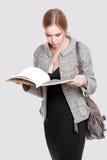 piękna biznesowej kobiety blondynka w czerni sukni, kurtka czyta magazyn na szarym tle obraz stock