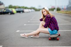 Piękna blond dziewczyna jest ubranym w kratkę koszula, nakrętkę i drelichowych skróty, siedzi na longboard na parking samochodowy fotografia royalty free