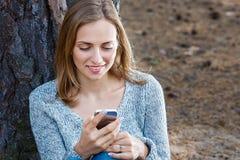 Piękna blond dziewczyna odpoczywa w lesie mówi telefonem komórkowym i, siedzący z filiżanką herbata i książka Ufny caucasian Zdjęcie Stock