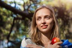 Piękna blond dziewczyna odpoczywa w wiosny lub jesieni lesie z czerwonym jabłkiem w ona ręki Ufna caucasian młoda kobieta wewnątr Obrazy Stock
