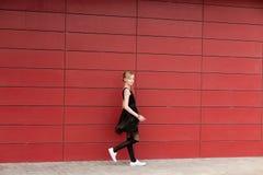 Piękna blond dziewczyna w czarnej sukni pozuje przeciw czerwonej ścianie Obraz Stock