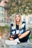 Piękna blond dziewczyna z dużą dużą pastylką w ręce i uśmiechem zdjęcia stock