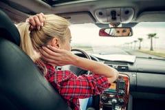 Piękna blond dziewczyny grępla jej włosy z rearview lustrem w samochodzie Obraz Royalty Free