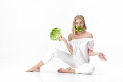 Piękna blond kobieta je świeżej zielonej sałatki na białym tle w białej bluzce diet zdrowie Zdjęcie Royalty Free
