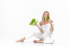 Piękna blond kobieta je świeżej zielonej sałatki na białym tle w białej bluzce diet zdrowie Zdjęcia Stock