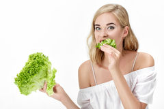 Piękna blond kobieta je świeżej zielonej sałatki na białym tle w białej bluzce diet zdrowie Zdjęcie Stock