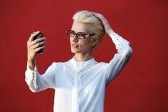 Piękna blond kobieta patrzeje telefon komórkowego Zdjęcia Royalty Free