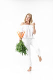 Piękna blond kobieta trzyma świeżej marchewki z zielenią opuszcza na białym tle diet zdrowie Obrazy Stock