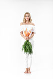 Piękna blond kobieta trzyma świeżej marchewki z zielenią opuszcza na białym tle diet zdrowie Obraz Stock