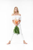 Piękna blond kobieta trzyma świeżej marchewki z zielenią opuszcza na białym tle diet zdrowie Obraz Royalty Free