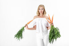 Piękna blond kobieta trzyma świeżej marchewki z zielenią opuszcza na białym tle diet zdrowie Zdjęcie Royalty Free