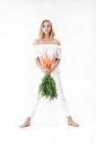 Piękna blond kobieta trzyma świeżej marchewki z zielenią opuszcza na białym tle diet zdrowie Zdjęcia Stock