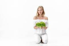 Piękna blond kobieta trzyma świeżej zielonej sałatki na białym tle w białej bluzce diet zdrowie Fotografia Royalty Free