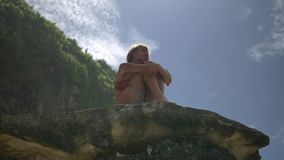 Piękna blond kobieta ustawia na skale na dzikiej plaży Bali zdjęcie wideo