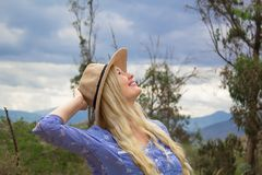 Piękna blond kobieta w kapeluszu Stoi na prerii, spojrzeniach przy niebem i uśmiechach, zdjęcia stock